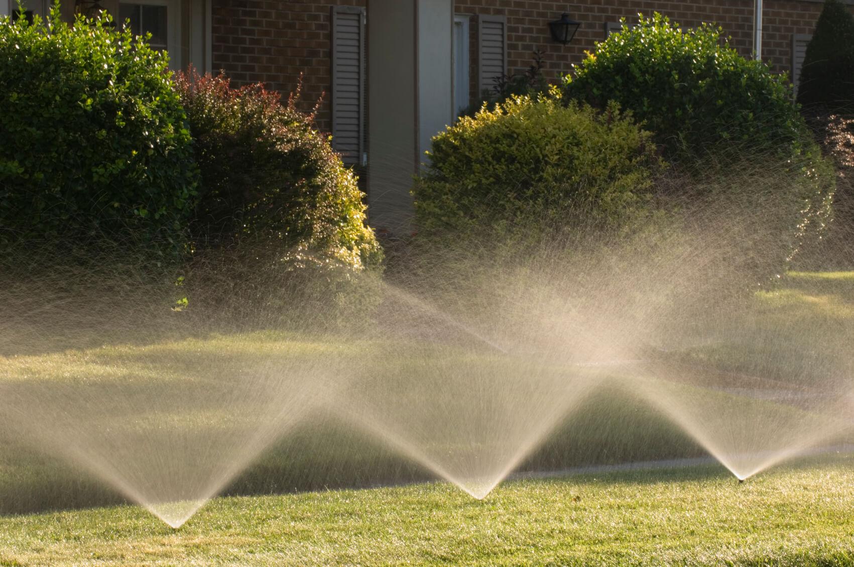 three sprinklers sprinkling water on a lawn
